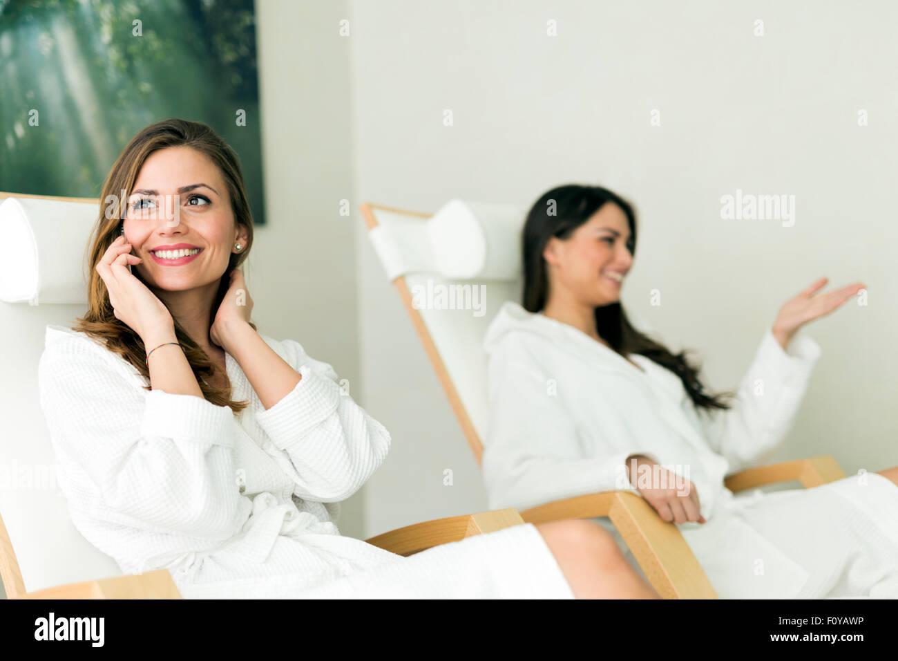 Giovani e belle donne rilassante in una spa che indossa le vesti e parlando al telefono Immagini Stock