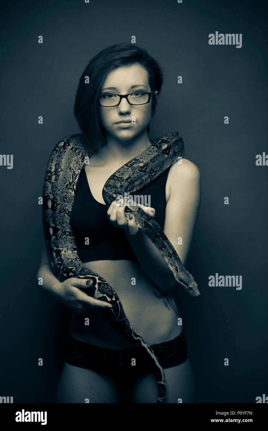 Una giovane donna ragazza persona di sesso femminile che indossano occhiali in posa con snake , NEL REGNO UNITO Immagini Stock