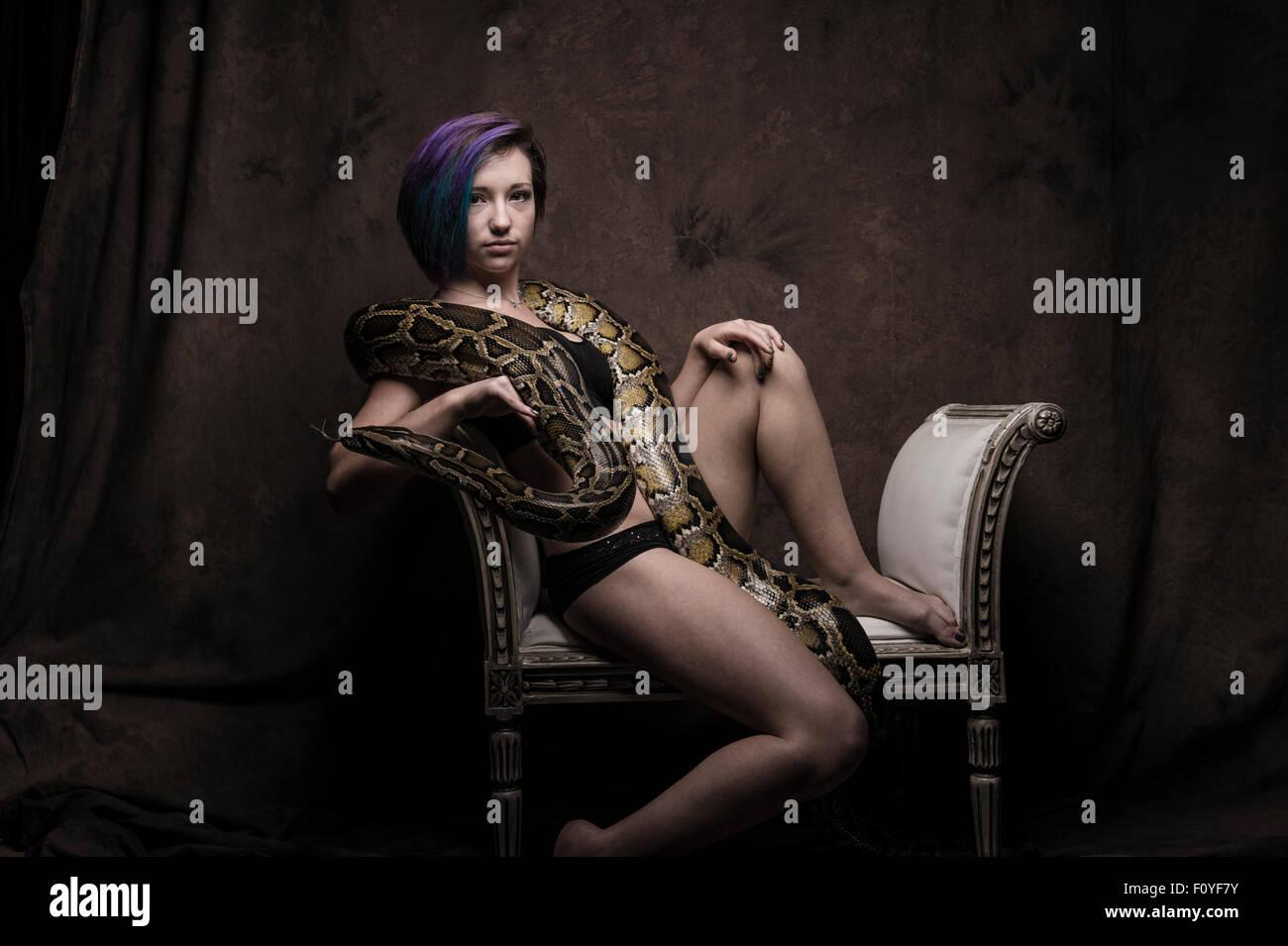 Una giovane donna ragazza persona di sesso femminile in posa seduto in una sedia con un serpente , NEL REGNO UNITO Immagini Stock