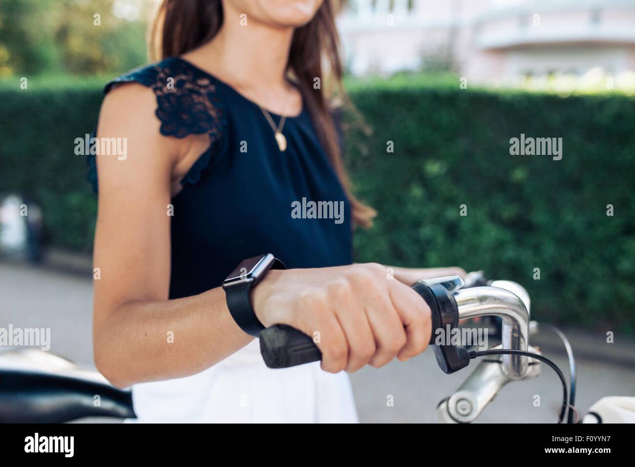 La donna in sella a una moto con un smartwatch. Indossare femmina smart a guardare mentre il ciclismo. Immagini Stock