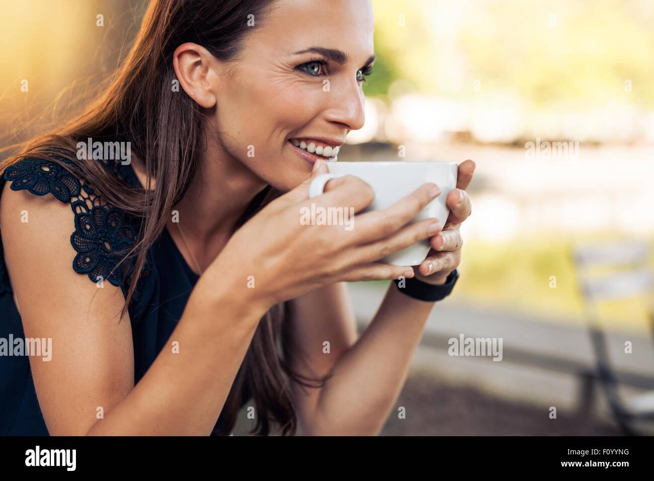 Giovane donna in possesso di una tazza di caffè e guardando lontano sorridente. Femmina caucasica di bere il Immagini Stock