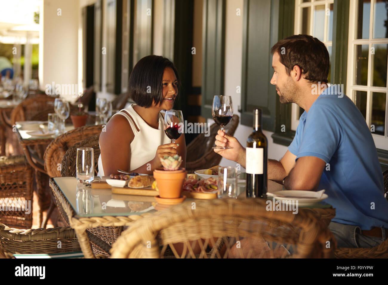 Maschio e femmina seduti al ristorante azienda bicchieri da vino e parlare. Coppia avente un vino rosso presso il Immagini Stock