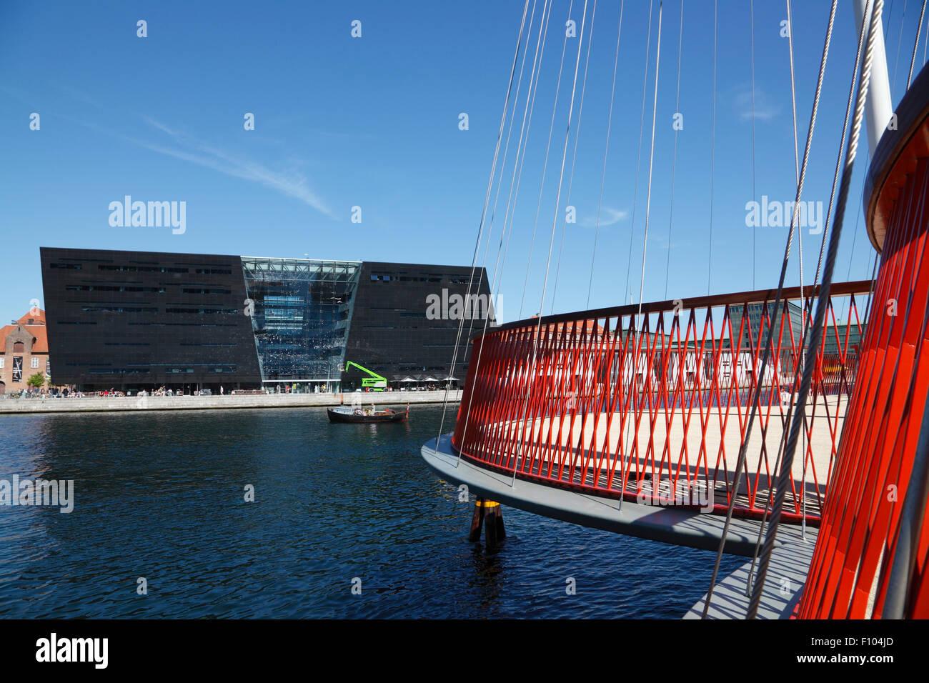 Cirkelbroen, il cerchio Bridge, progettato da Olafur Eliasson spanning Christianshavn Canal. Il Diamante Nero, Den Sorte Diamant, in background. Foto Stock