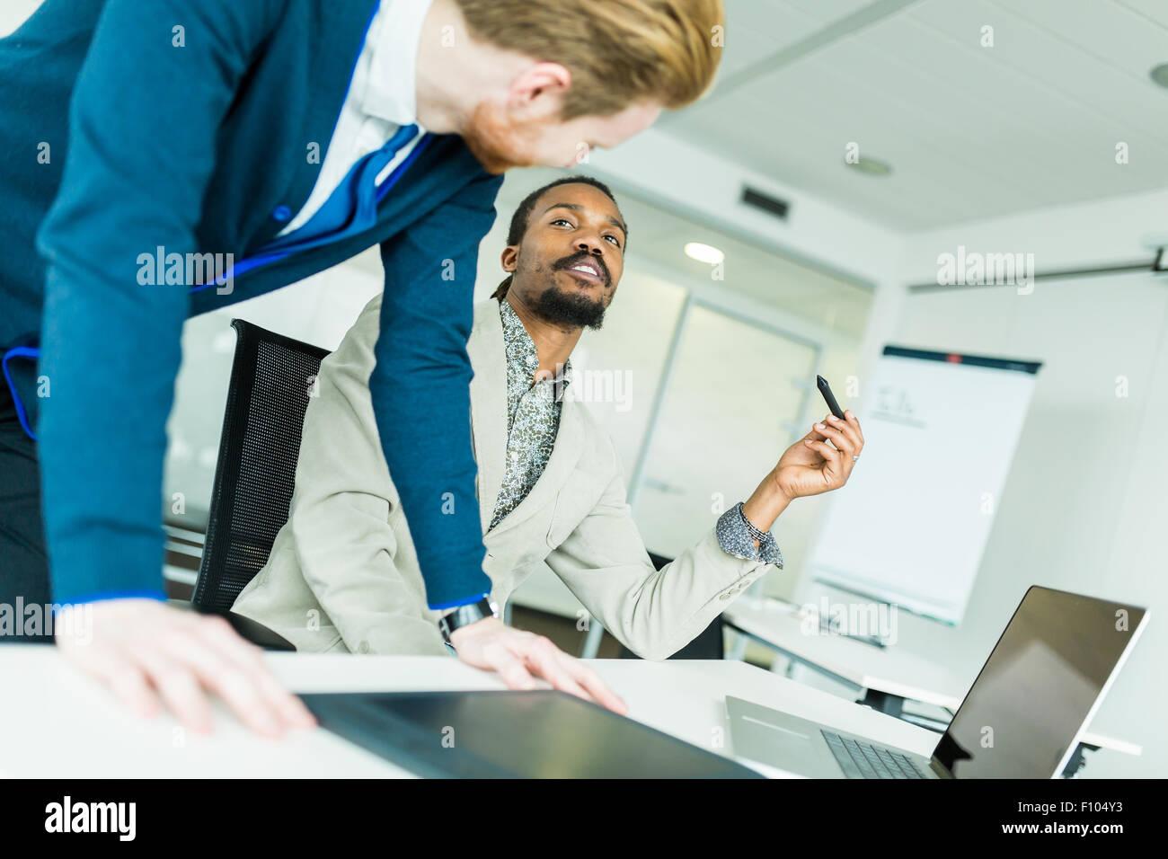 Un nero giovane con dreadlocks e un giovane bello dai capelli rossi imprenditore a discutere di grafica difetti Immagini Stock