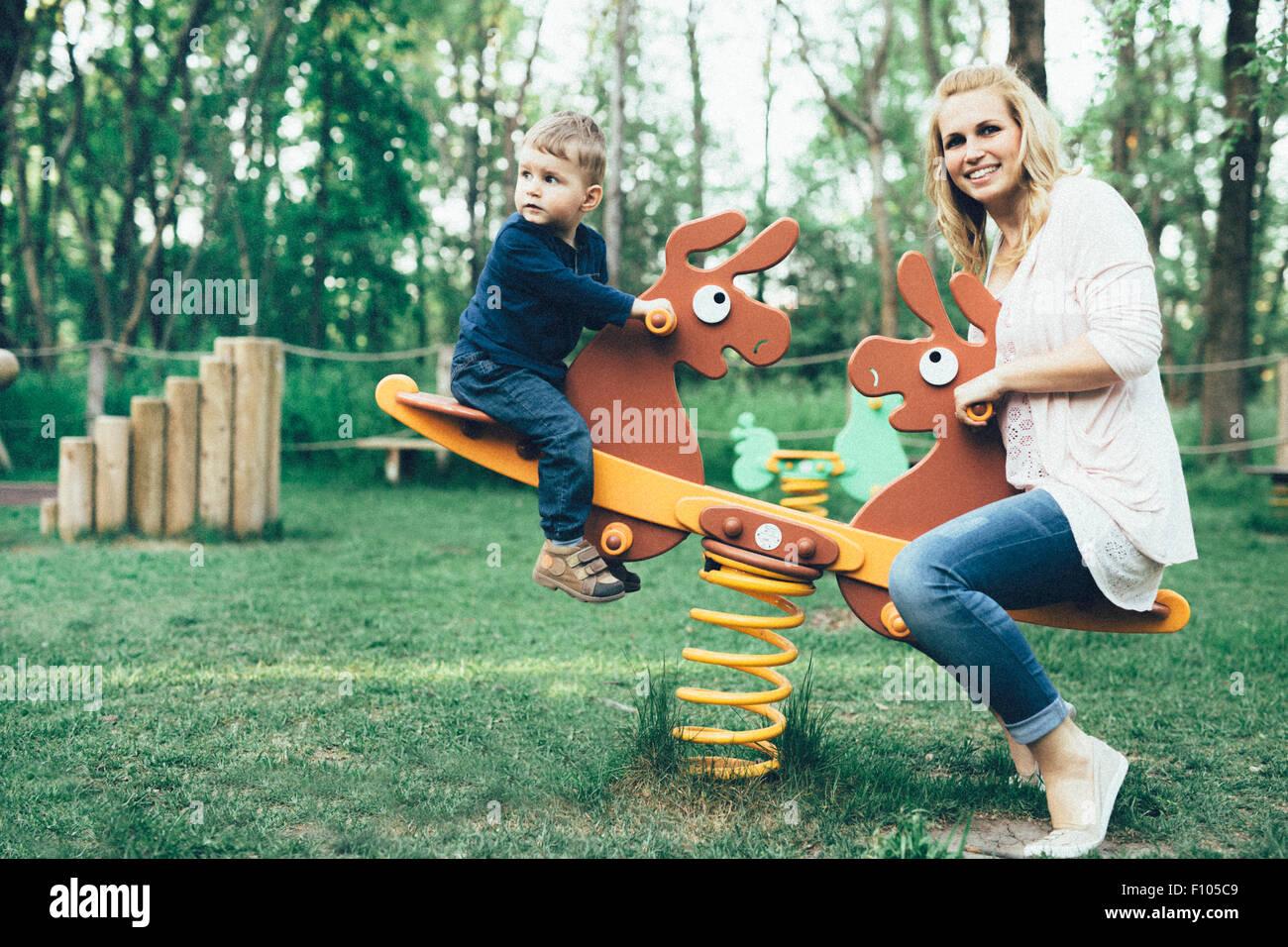 La madre e il figlio a giocare nel parco giochi e a cavallo di un altalena Immagini Stock