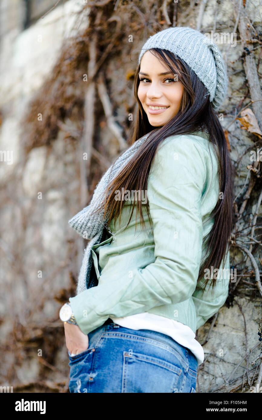 Ritratto di una giovane donna bella in autunno come ambiente appoggiato contro una parete Immagini Stock