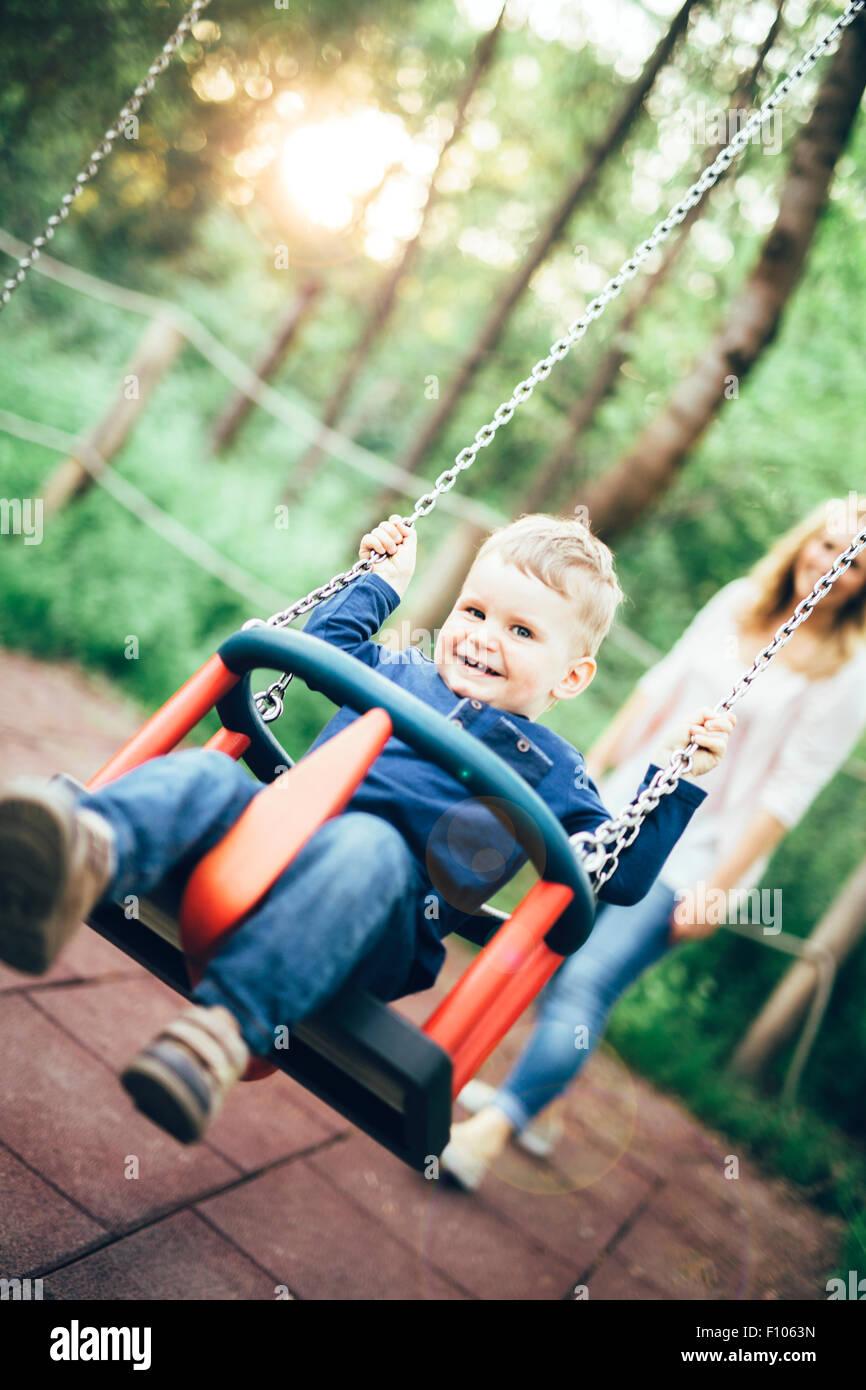 La madre e il bambino all'aperto nel parco giochi a cavallo di un swing e sorridente Immagini Stock