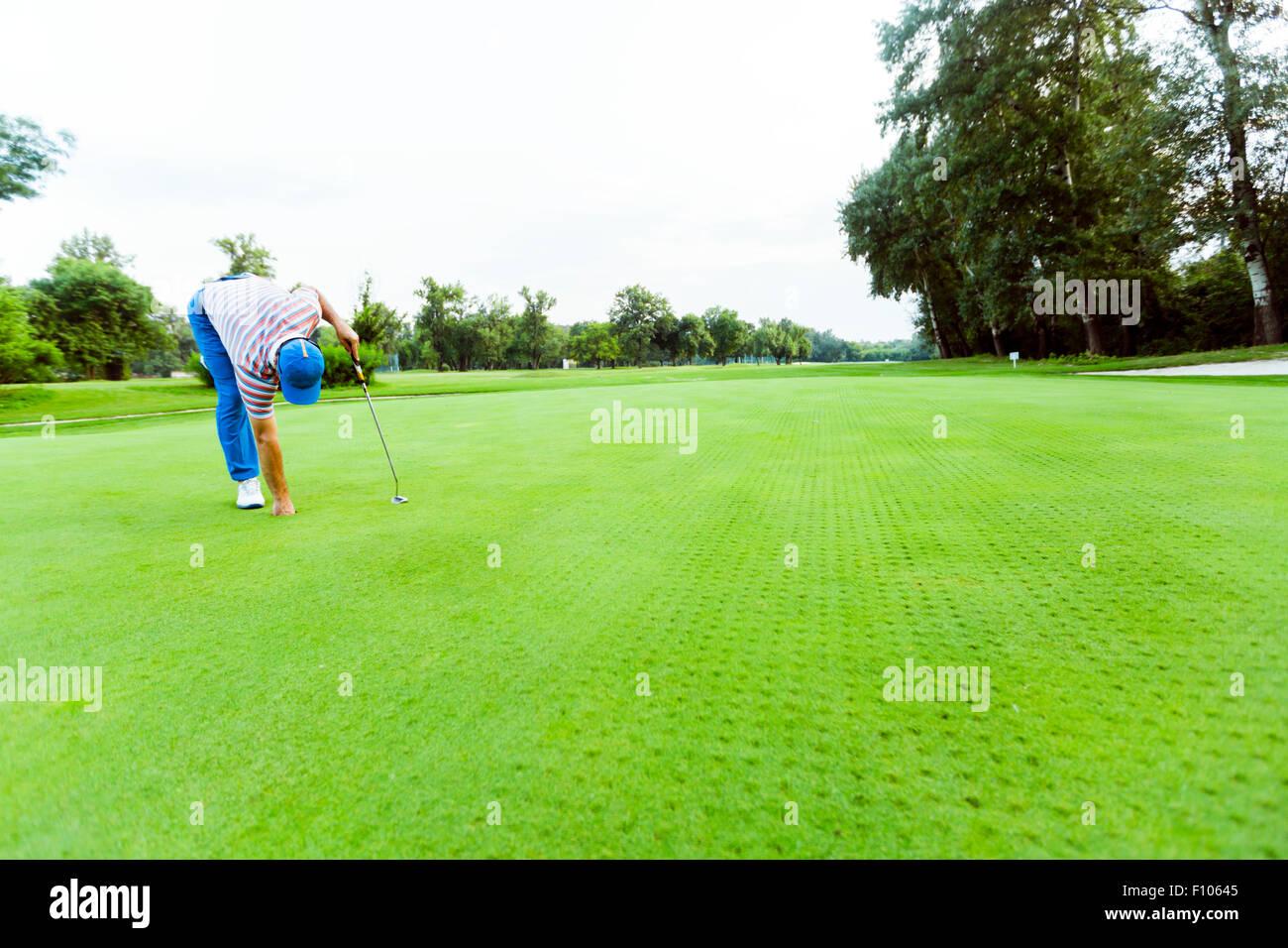 Il Golfer recuperando la sfera dal foro su un bel corso Immagini Stock