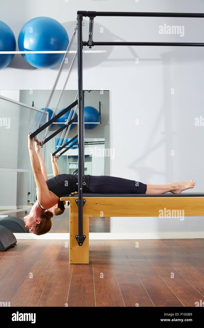 Pilates donna nel reformer esercizio in palestra indoor Immagini Stock