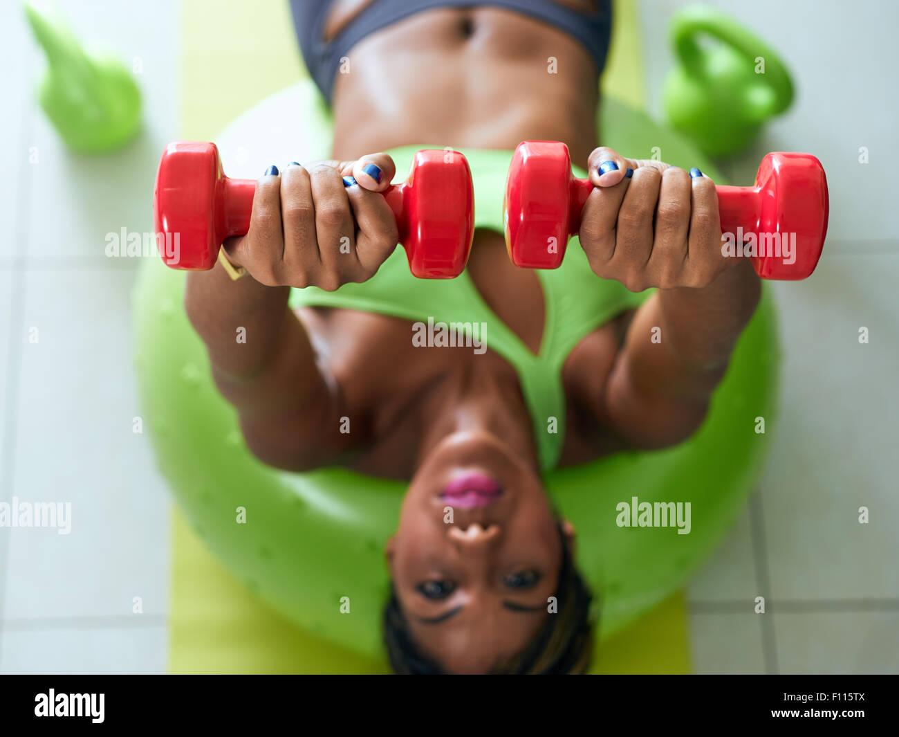 Giovane adulto americano africano donna in abbigliamento sportivo a casa, facendo fitness domestico e la formazione Immagini Stock