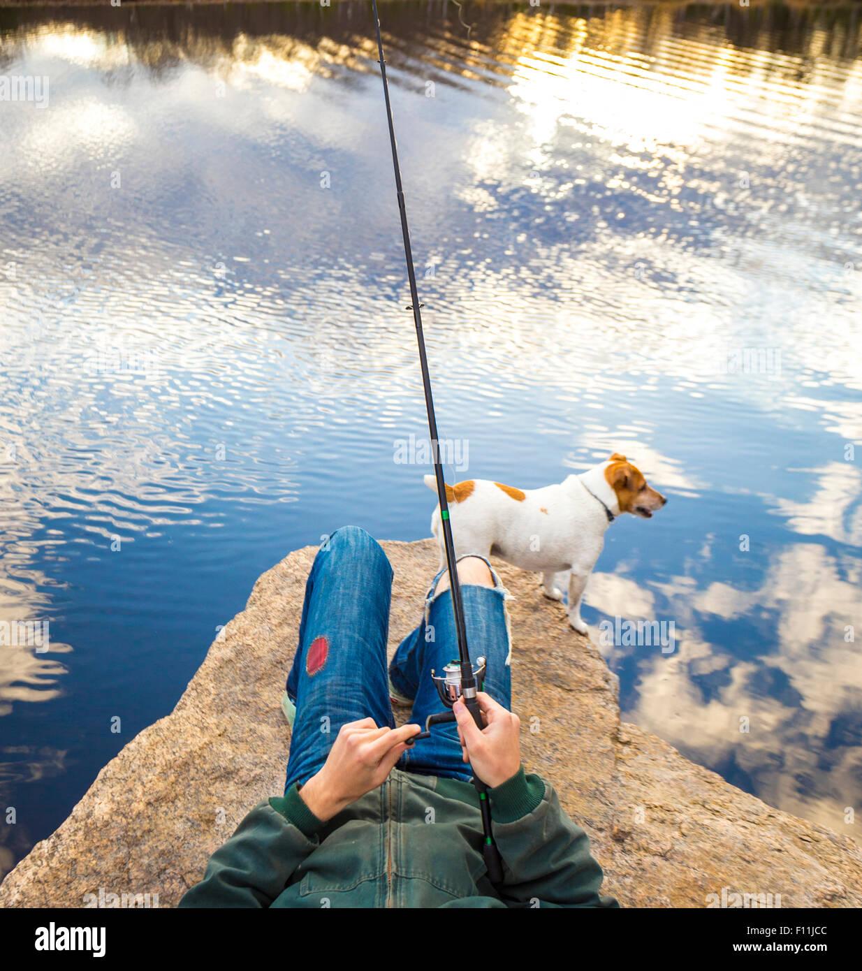 Uomo caucasico la pesca con il cane nel lago in remoto Immagini Stock