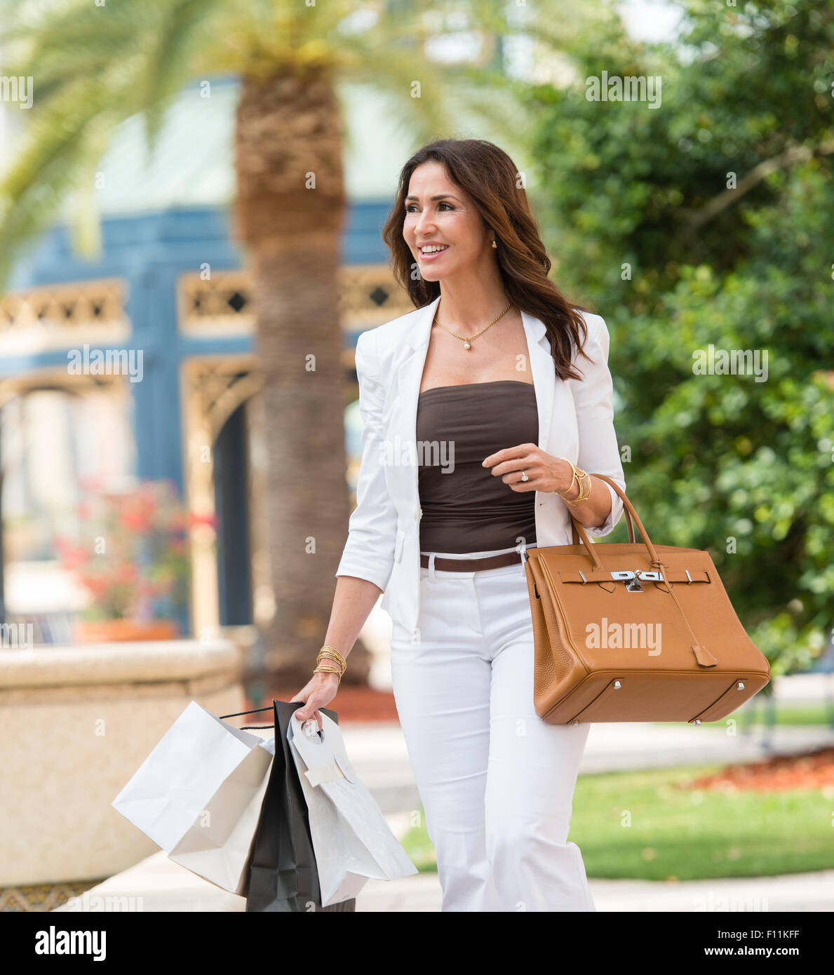 Donna ispanica il trasporto delle borse della spesa e portamonete Foto Stock