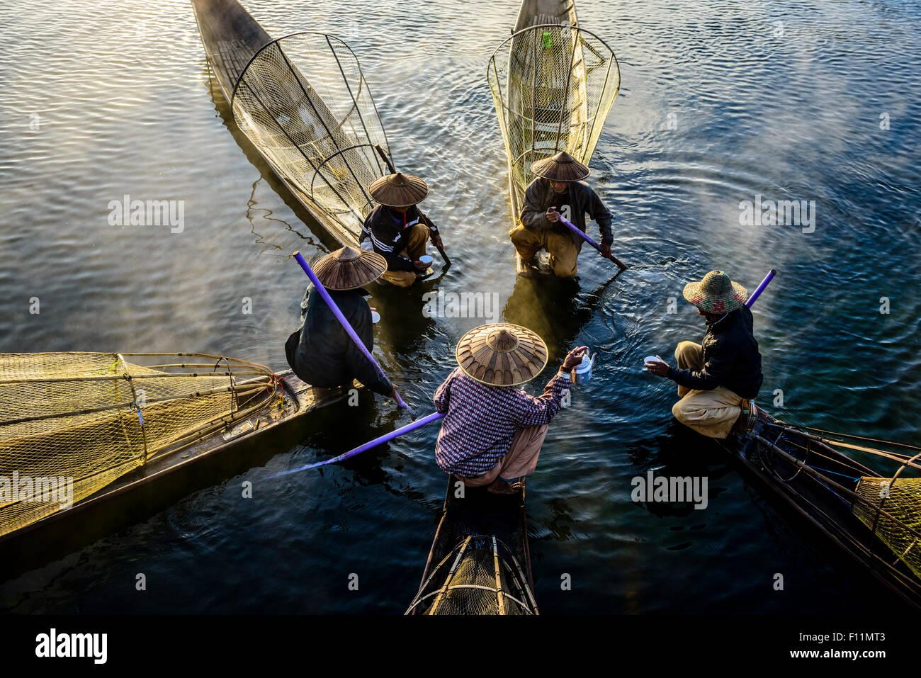 Angolo di alta vista di Asian pescatori pesca in canoa sul fiume Immagini Stock