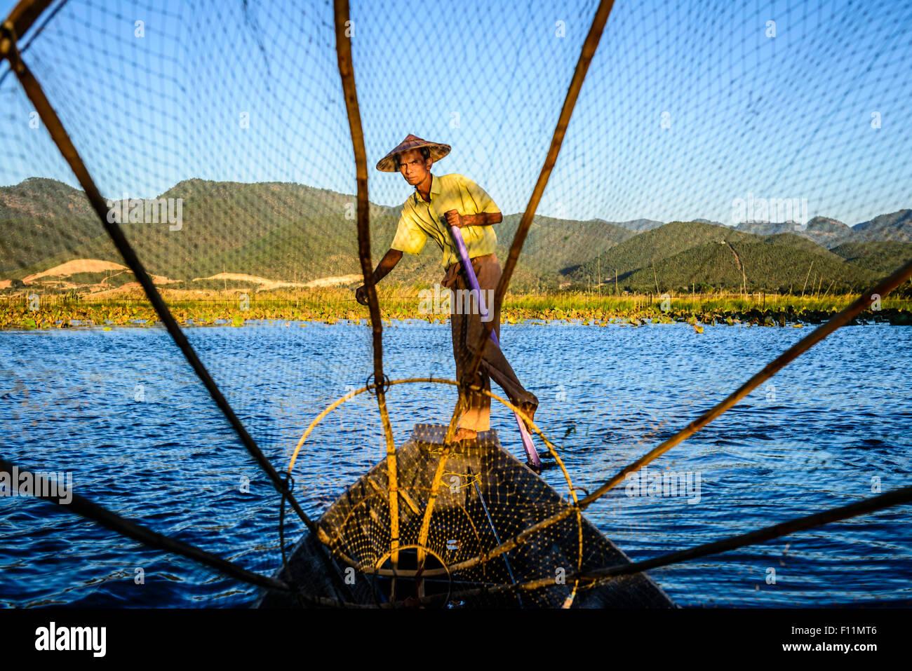 Asian pescatore con rete da pesca in canoa sul fiume Immagini Stock