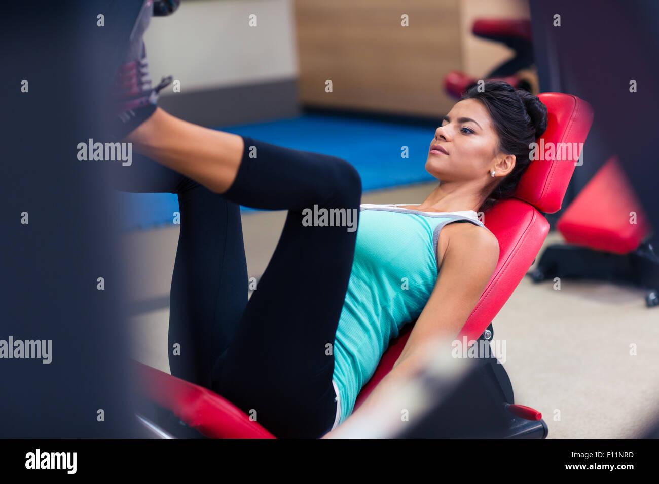 Ritratto di una donna sportiva allenamento sulla macchina di esercizi in palestra per il fitness Immagini Stock