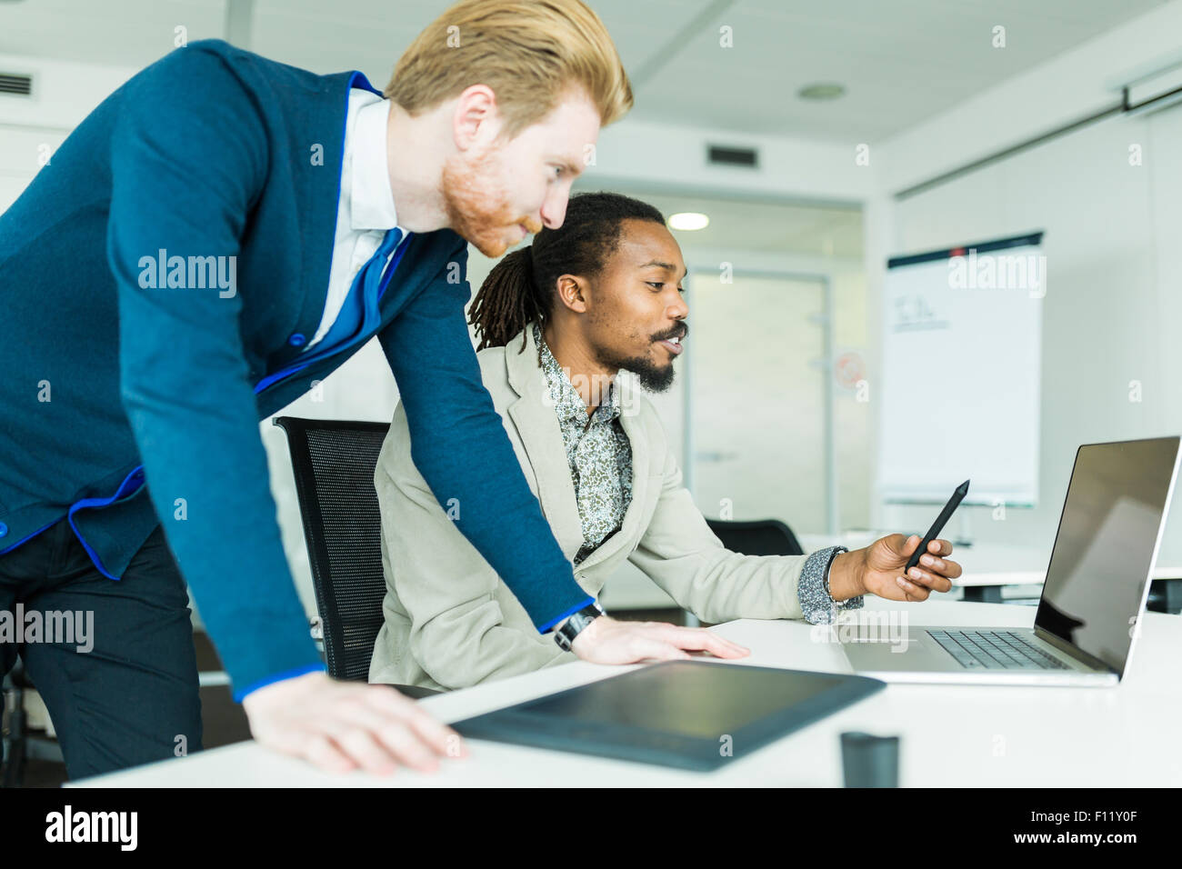Un nero giovane con dreadlocks e un giovane bello dai capelli rossi imprenditore per discutere la progettazione Immagini Stock