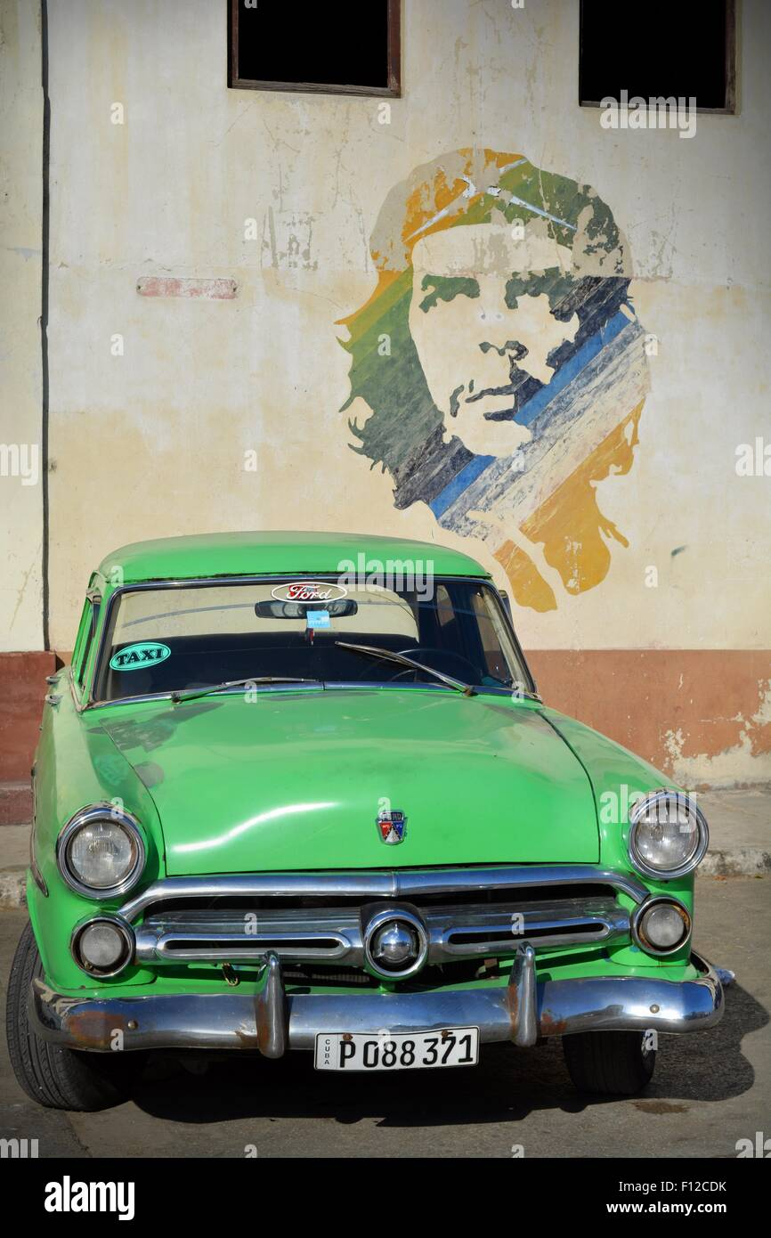Vintage Ford verde taxi parcheggiato al di sotto di Che Guevara murale nel parcheggio a l'Avana Vecchia Cuba Immagini Stock
