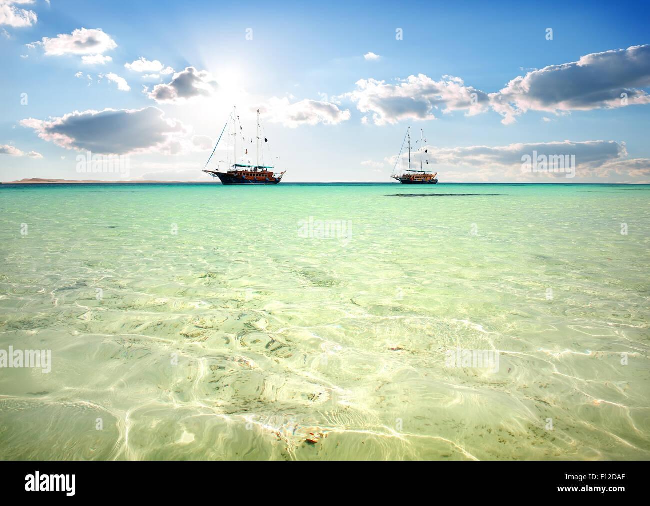 Due barche a vela in mare turchese sotto la luce del sole Immagini Stock