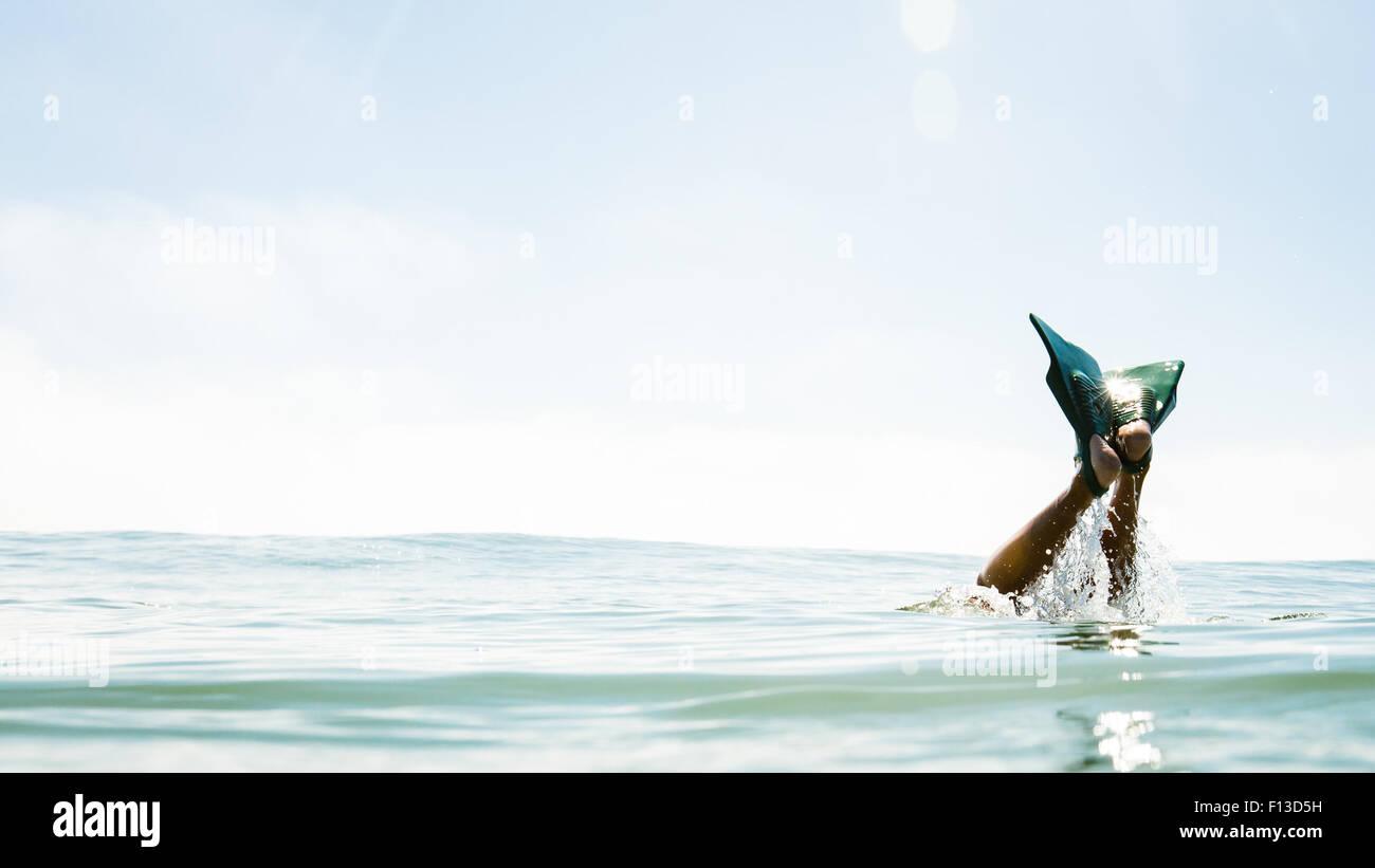 Gambe umane con pinne fuori del mare Immagini Stock