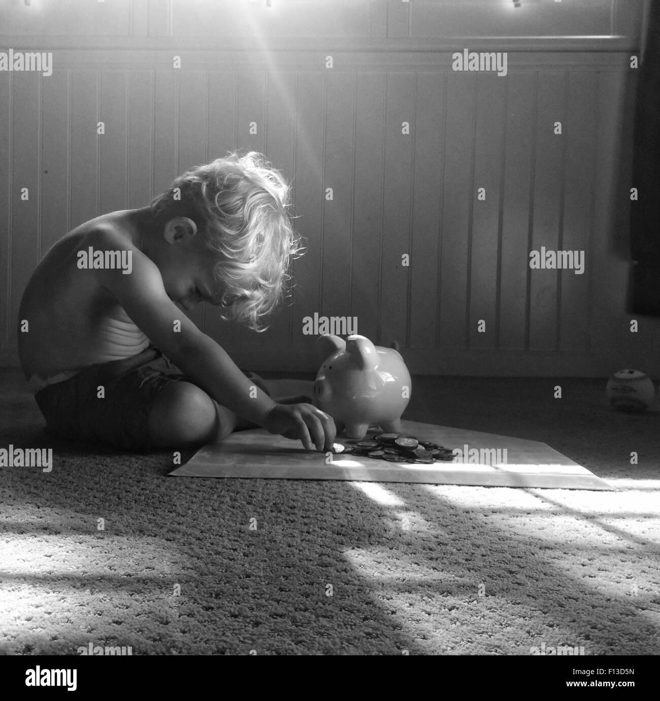 Bambino seduto sul pavimento conteggiare denaro Immagini Stock