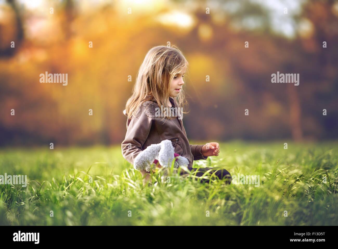 Ragazza seduta in un campo tenendo un giocattolo morbido Immagini Stock