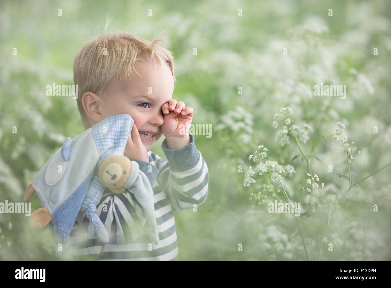 Stanco bambino in piedi in un campo strofinando i suoi occhi Immagini Stock