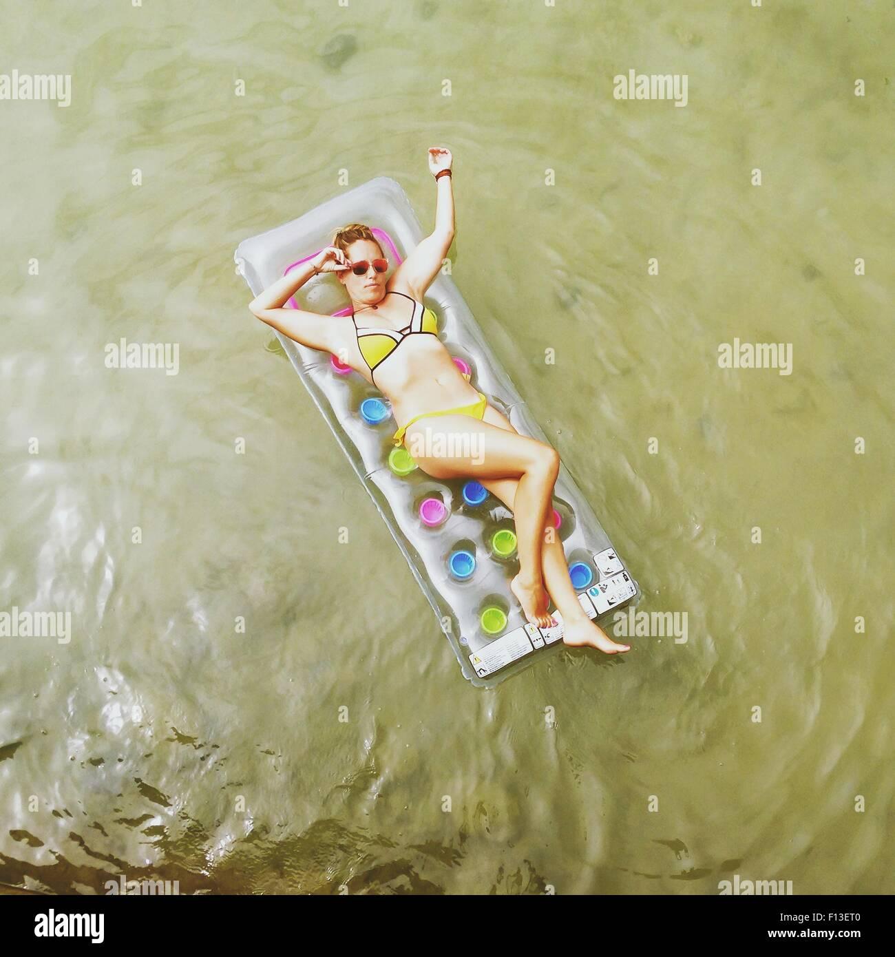 Vista aerea di una donna sdraiata su un materasso gonfiabile in mare Immagini Stock