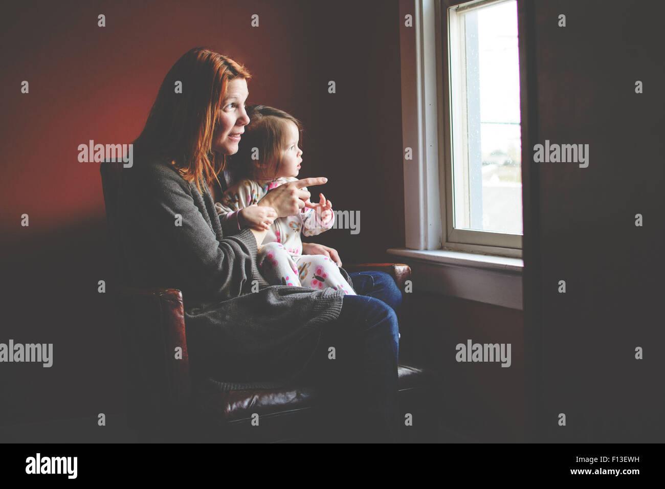 Baby ragazza seduta sulla sua madre giro, guardando fuori dalla finestra Immagini Stock