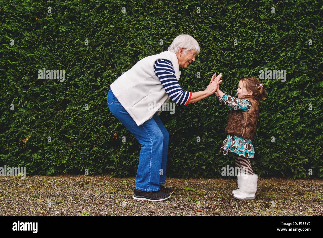 Ragazza che gioca pat-a-la torta con la sua nonna Immagini Stock