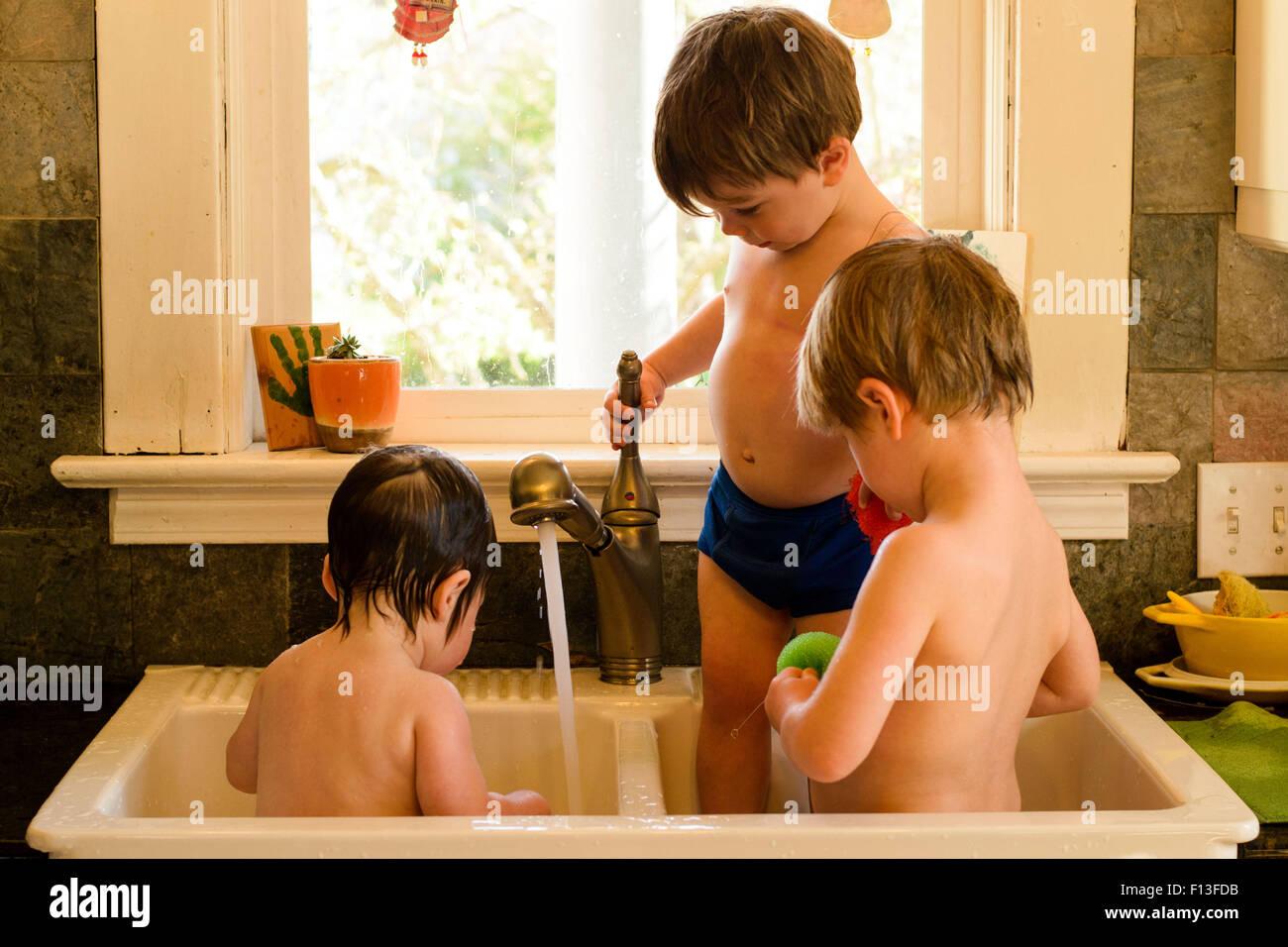 Tre bambini in un dissipatore di maggiordomi avente un lavaggio Immagini Stock
