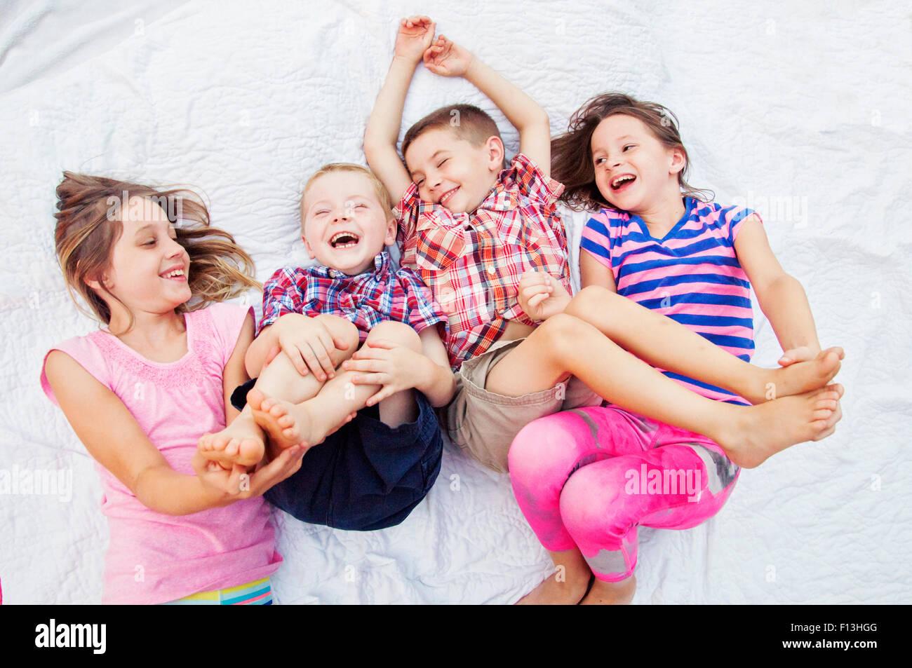 Due sorelle tickle due fratelli piedi Immagini Stock