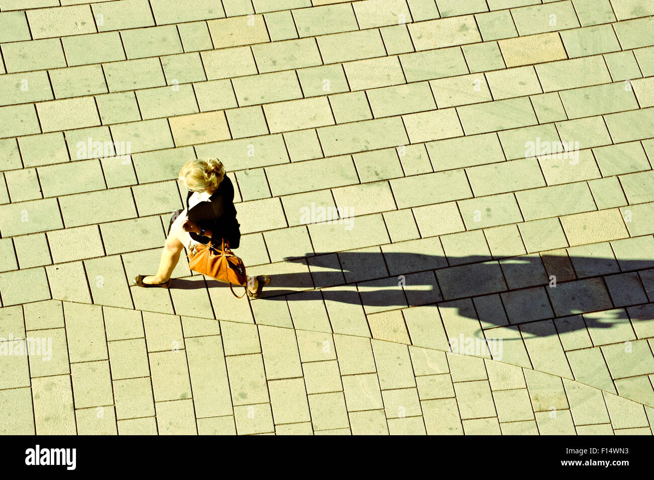 Donna che cammina sulla strada, proiettando una lunga ombra. Visto dal di sopra Immagini Stock