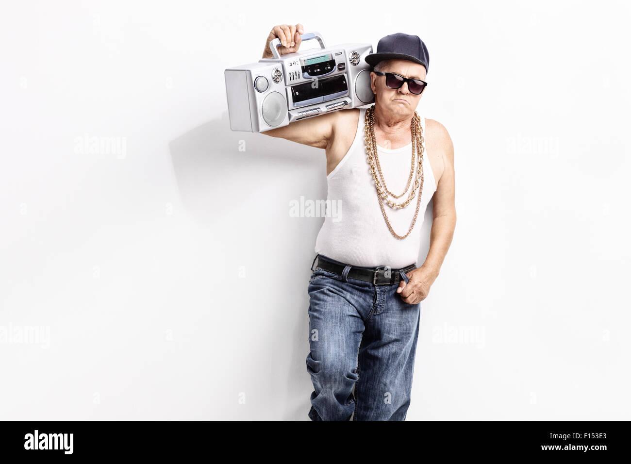 Uomo Senior in un hip-hop vestito che trasportano ghetto blaster sulla sua  spalla e guardando la telecamera 98a14c80be0f