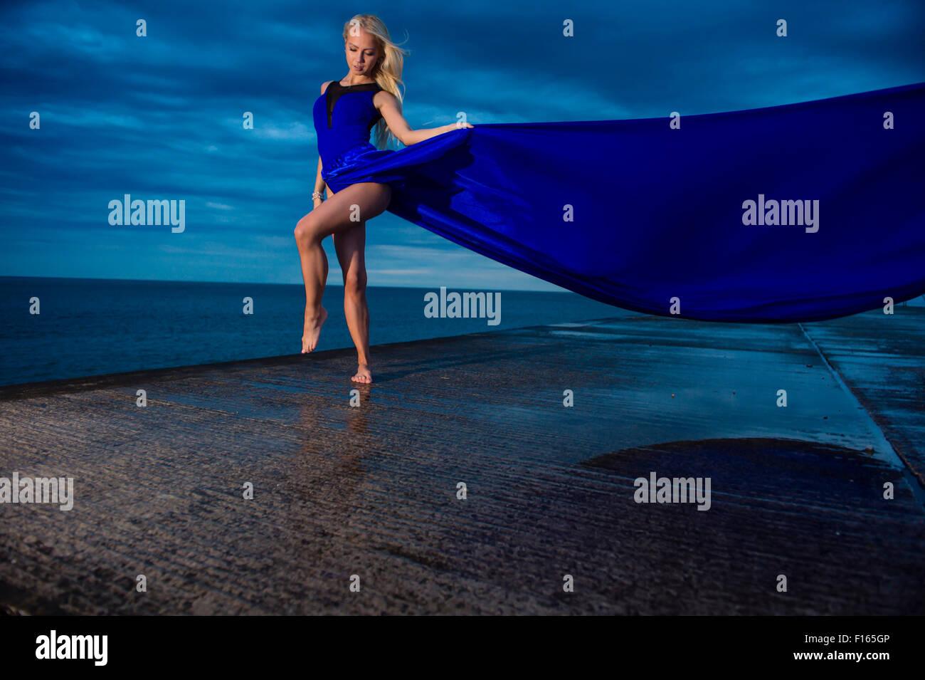 Posizione esterna fotografia - un alto slim bionda bionda donna modello ragazza in posa all'aperto su una serata Immagini Stock