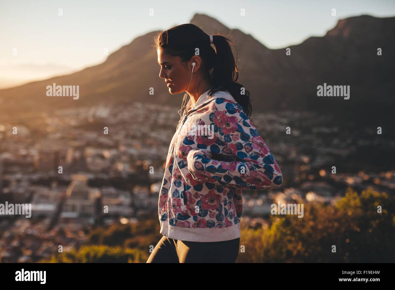 Vista laterale della giovane donna caucasica sulla passeggiata mattutina. Donna passeggiate all'aperto. Uno Immagini Stock
