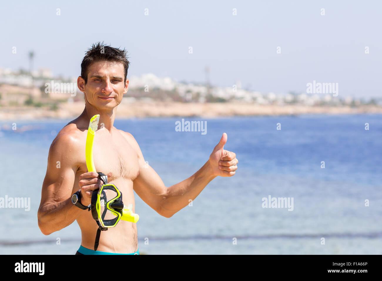 Giovane uomo sorridente detiene l'equipaggiamento da snorkeling e mostra il pollice verso l'alto. La vacanza Immagini Stock