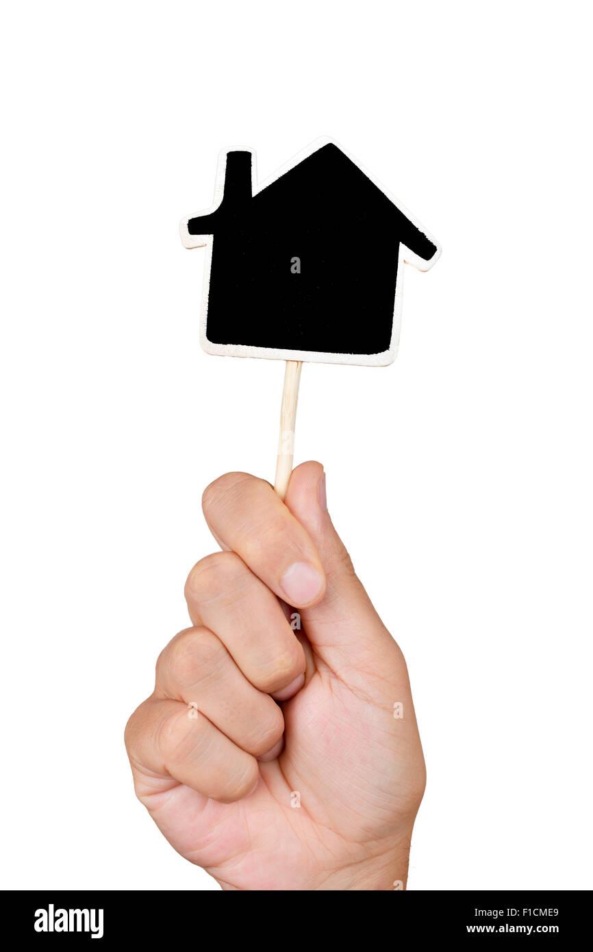 Primo piano della mano di un uomo giovane azienda una lavagna vuota a forma di casa, contro uno sfondo bianco Immagini Stock