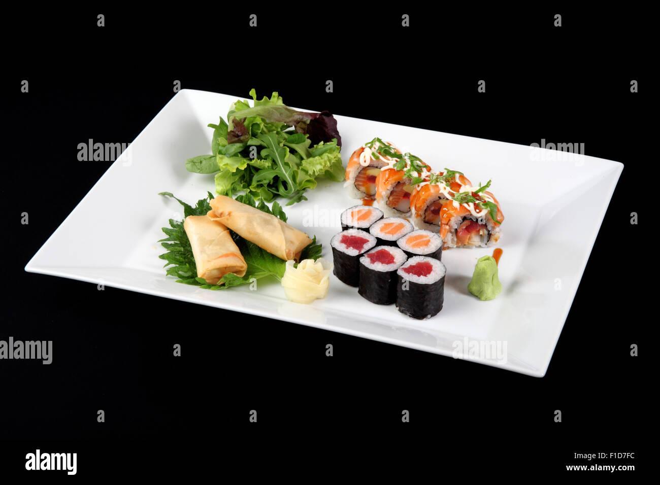 Menu di sushi e roll pesce con verdure e wasabi sulla piastra di bianco su nero Immagini Stock