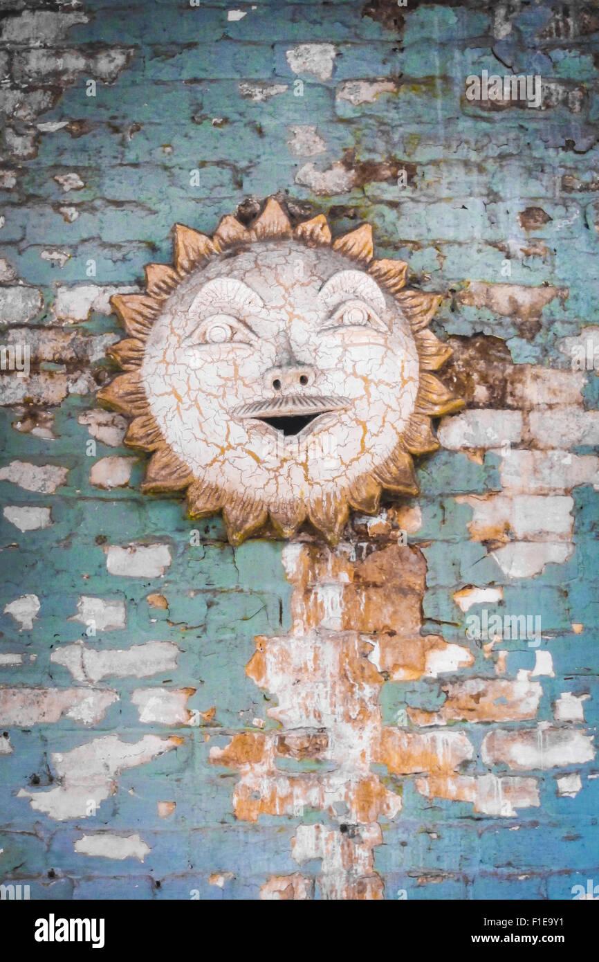 Sole in ceramica decorazioni a parete dipinta su un muro di mattoni Foto Stock