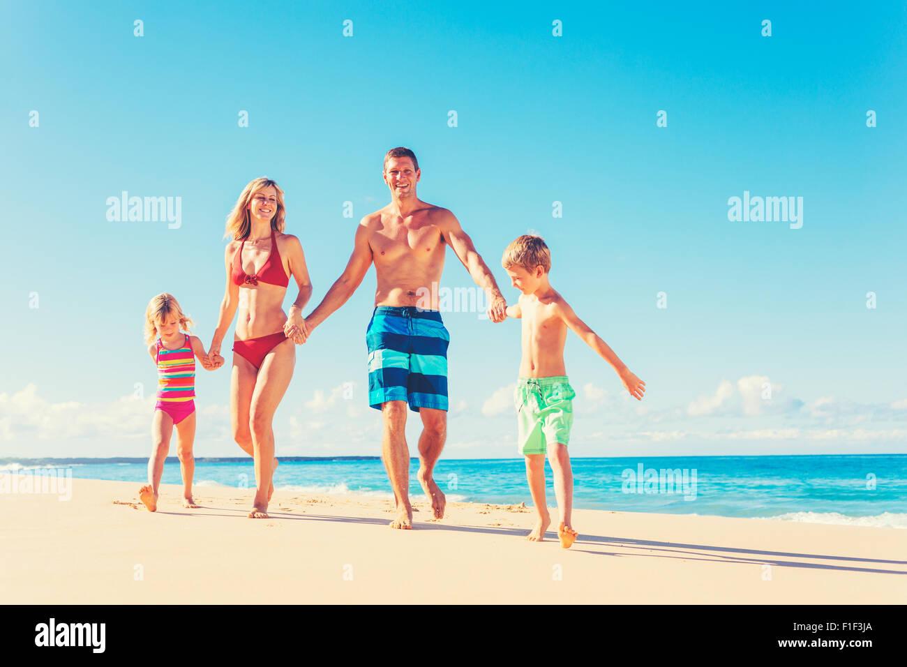 Vacanza in famiglia. La famiglia felice avendo divertimento sulla calda bella spiaggia soleggiata. Lo stile di vita Immagini Stock