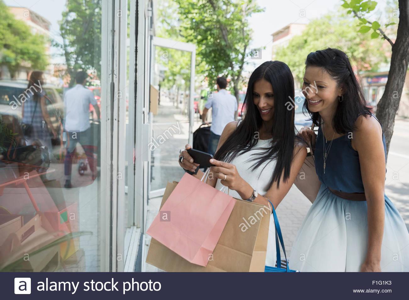 Le donne di fotografare la finestra di visualizzazione in vetrina Foto Stock