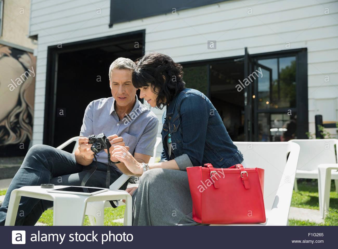 Giovane guardando alla fotocamera digitale sul patio soleggiato Immagini Stock