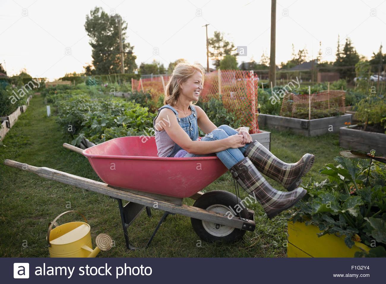 Donna sorridente plaid wellingtons seduta carriola giardino Immagini Stock