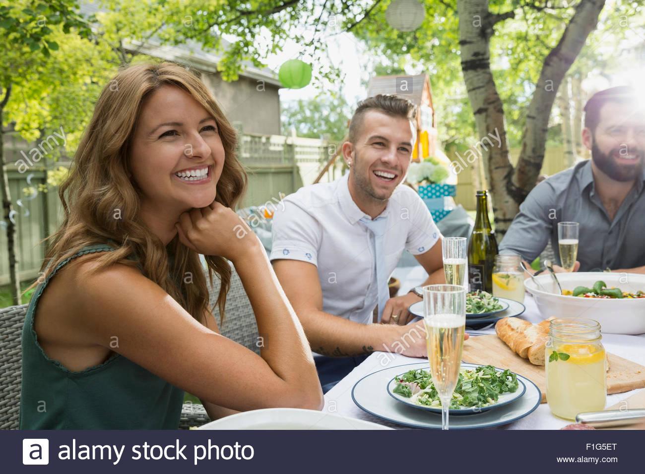 Sorridendo gli amici sorseggiando garden party pranzo Immagini Stock