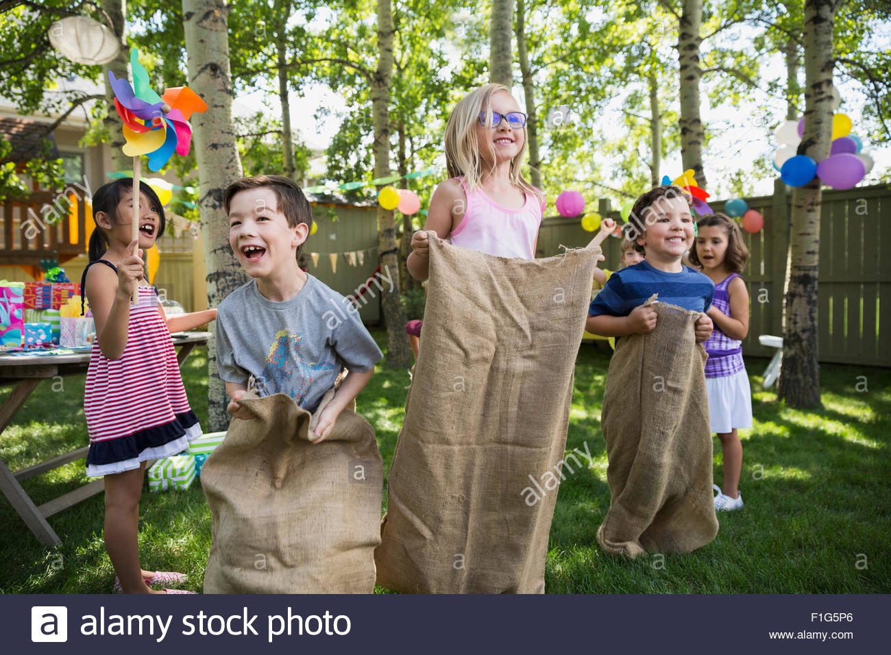 Kids godendo il sacco gara a backyard festa di compleanno Immagini Stock