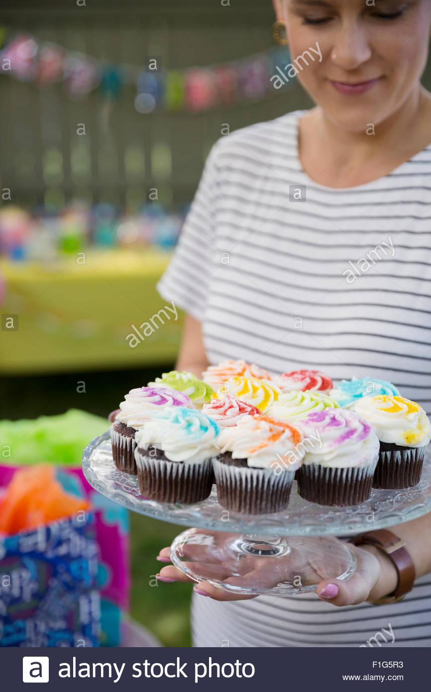 Donna che mantiene i tortini sulla torta stand Immagini Stock