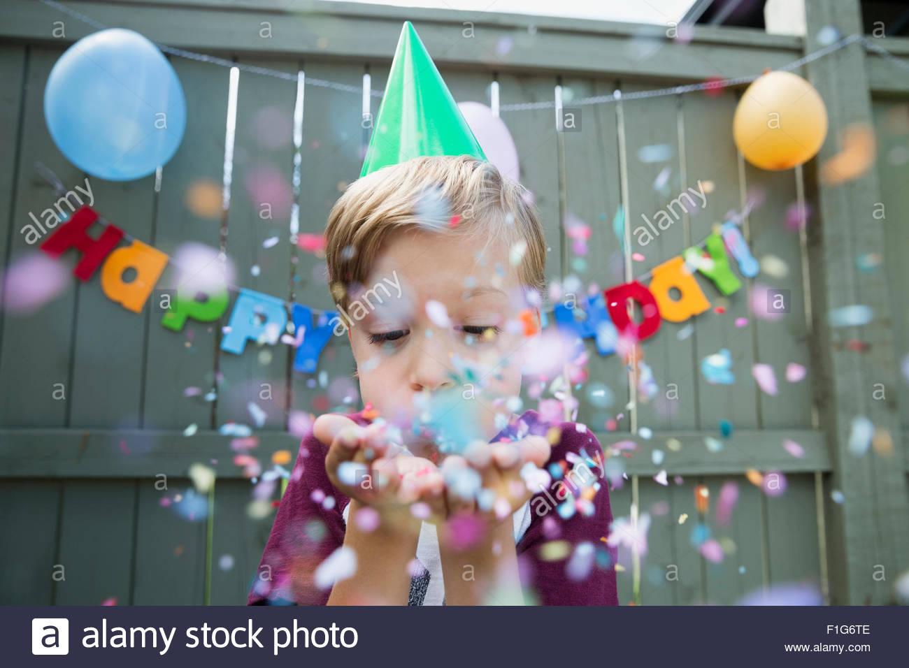 Ragazzo soffiando coriandoli indossando festa di compleanno hat Immagini Stock