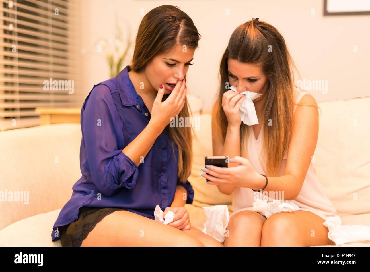 Due giovani donne, seduti sul divano guardando smartphone, sconvolto l'espressione Foto Stock