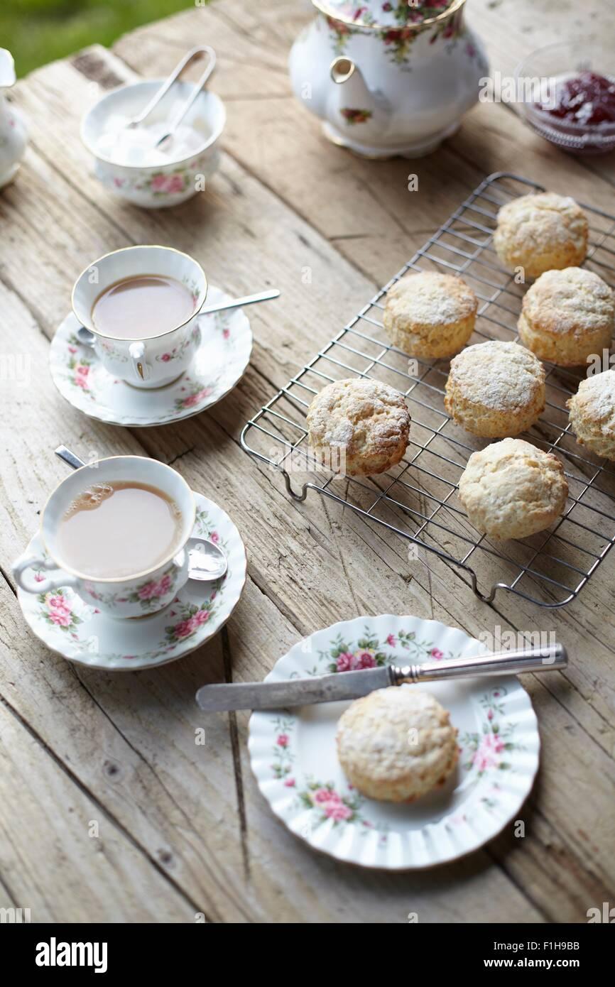 Tabella con focaccine fresche e il tè del pomeriggio Immagini Stock