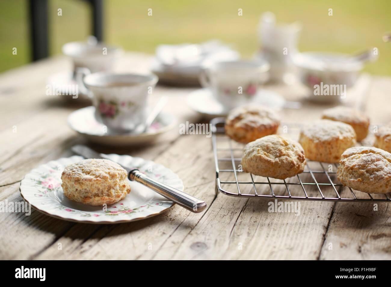 Tavolo con freschi di forno focaccine e tè del pomeriggio Immagini Stock